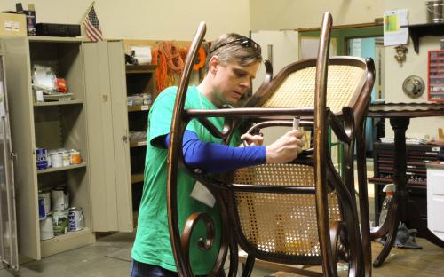 Paul Hoover repairs a chair